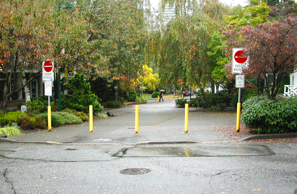 Bollards turn a 4-way junction into 3-way. Landscaping offers a relief.